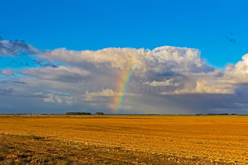Радуга и облака над вспаханным полем стоковые фото
