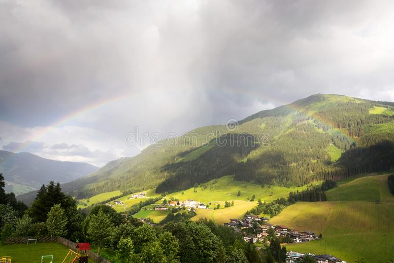 Радуга над долиной с горой Schattberg, Saalbach-Hinterglemm, Австрией стоковые изображения rf