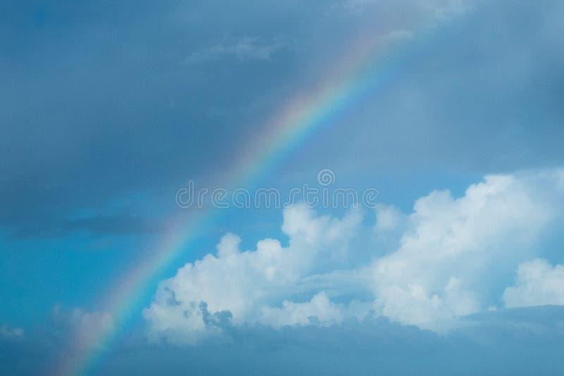 Радуга против предпосылки голубого неба с пушистыми белыми ливневыми облака стоковое фото rf