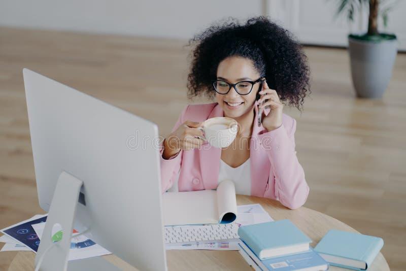 Радующаяся темнокожая бизнесменка счастливо смотрит на компьютер, пьет свежий горячий напиток, держит современный мобильный телеф стоковое изображение
