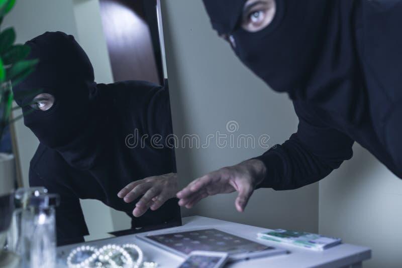 Разбойник в маске во время ограбления стоковое фото