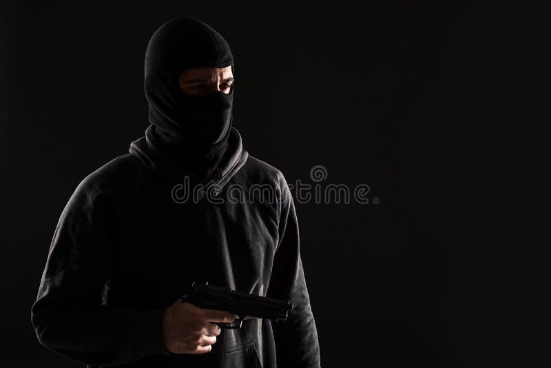 Разбойник в маске с оружием указал к стороне на черной предпосылке стоковые изображения rf