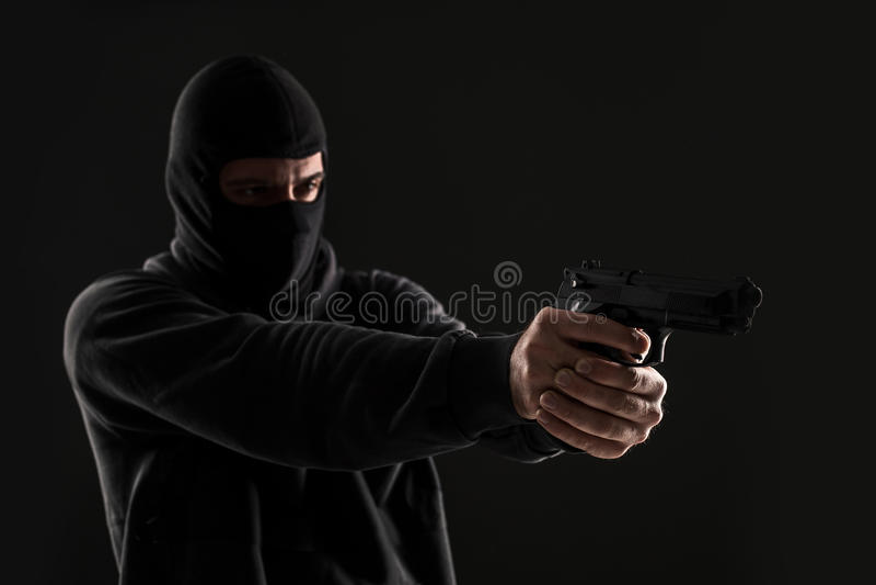 Разбойник в маске с оружием указал к стороне на черной предпосылке стоковое фото rf