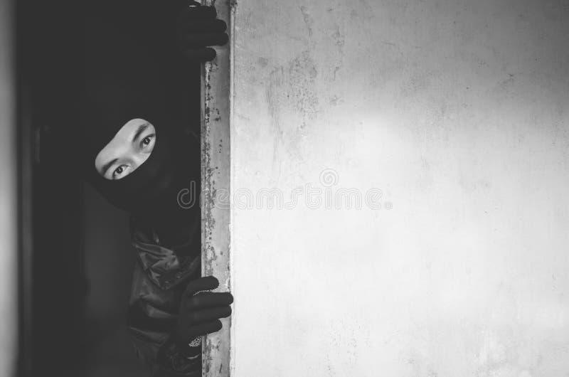 Разбойник человека, похититель в маске пряча за пустой стеной с космосом для текста стоковые фото