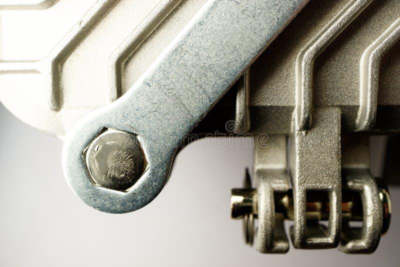 Разборка оборудования металла с ключем, вывинчивает болт шестиугольника стоковая фотография