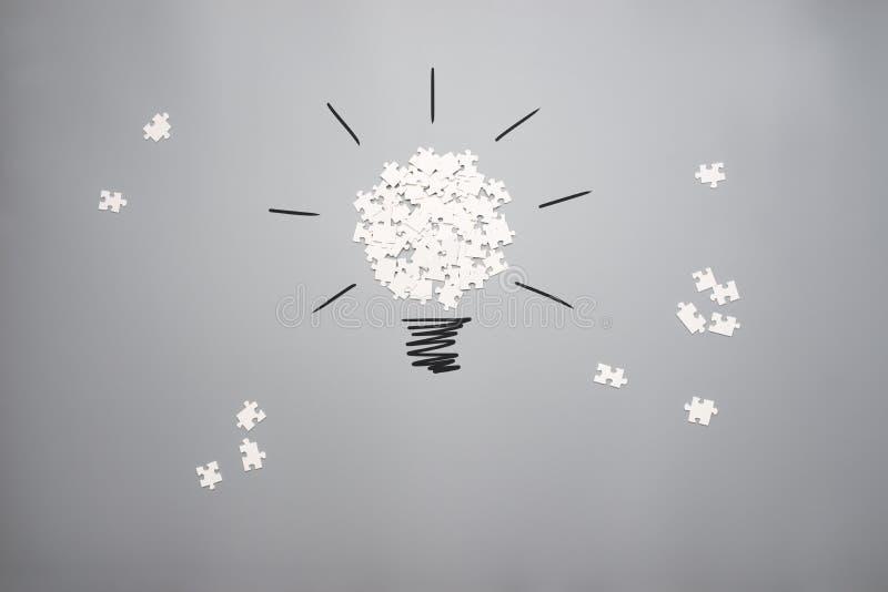 Разбросанная головоломка соединяет формировать электрическую лампочку на сером backgroun стоковое фото rf