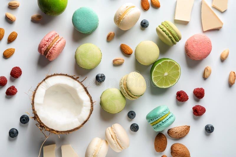 Разбросанные вкусные macaroons, кокос, ягоды и гайки на белой таблице стоковые изображения