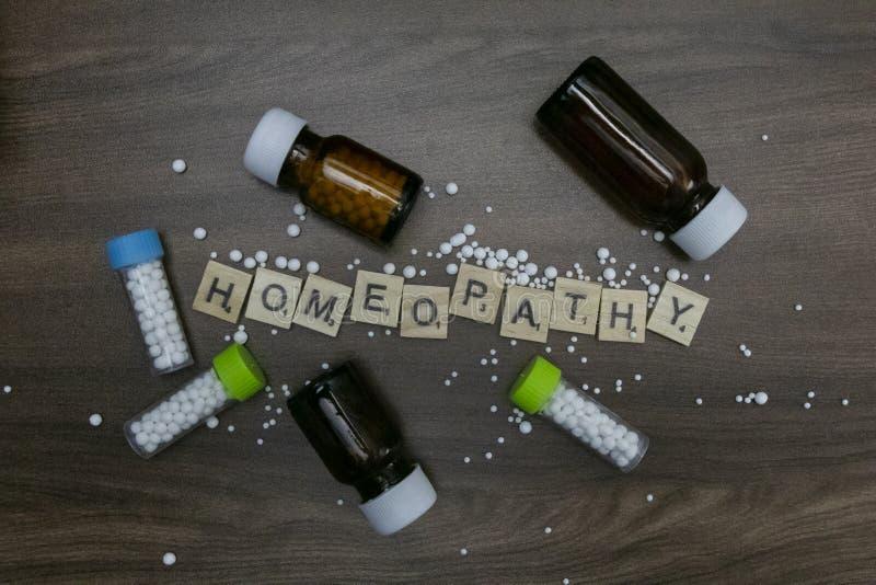 Разбросанные глобулы с гомеопатией бутылок и текста вещества гомеопатии на деревянной предпосылке стоковые изображения rf