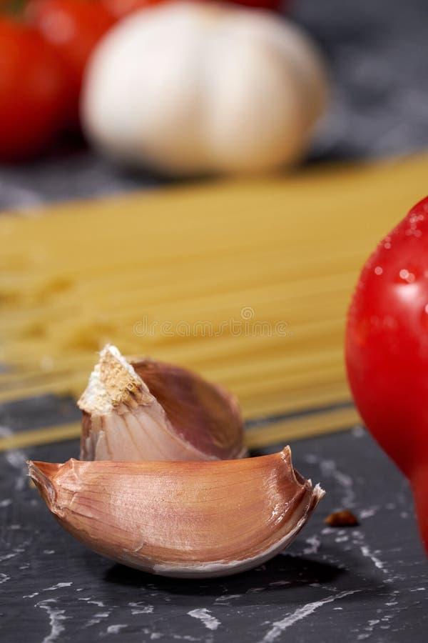 Разбросанные макаронные изделия, чеснок, томаты, на серой предпосылке стоковая фотография rf