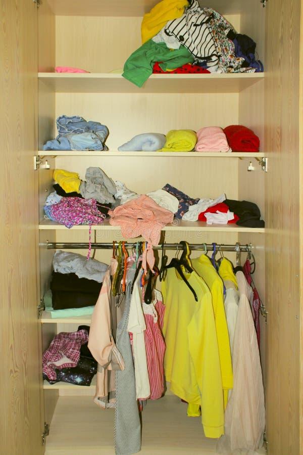 Разбросанные одежды в шкафе Одежды в уборной стоковые фото