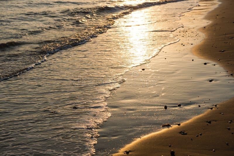 Развевает причаливая песчаный пляж во время захода солнца стоковые изображения