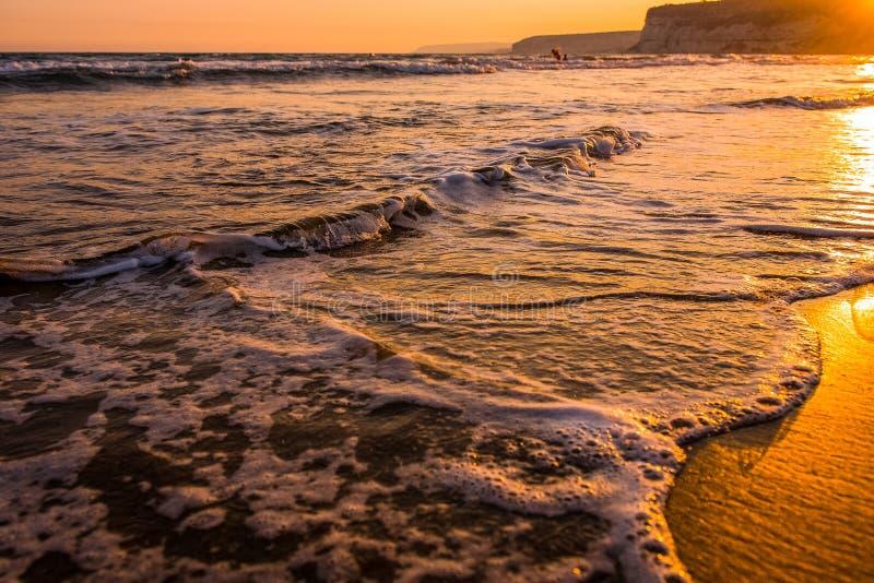 Развевает причаливая песчаный пляж во время захода солнца стоковая фотография rf