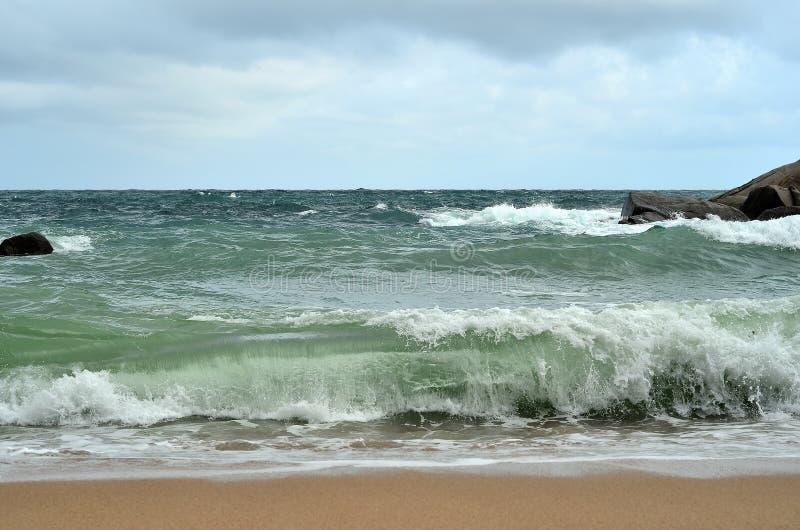 Развевайте разбивать против песчаного пляжа - сила природы стоковая фотография rf