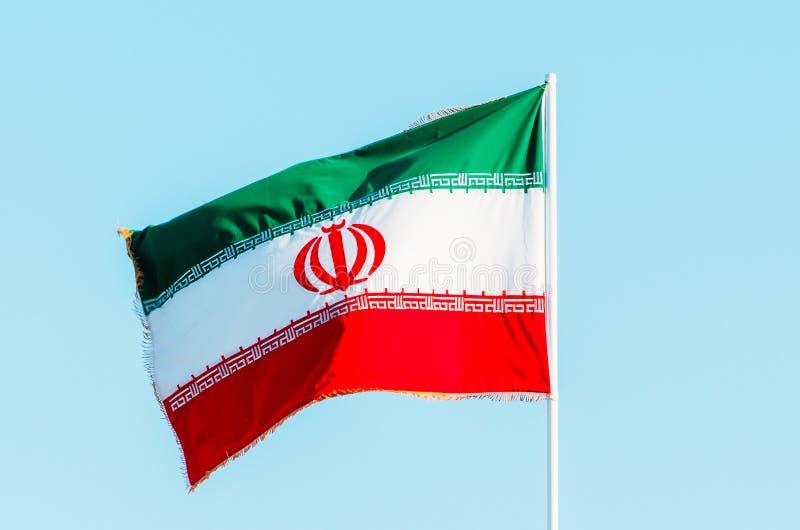 Развевая красочный флаг Ирана на голубом небе стоковые фото
