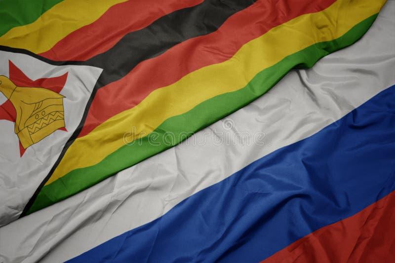 развевая красочный флаг России и национальный флаг Зимбабве стоковое изображение rf