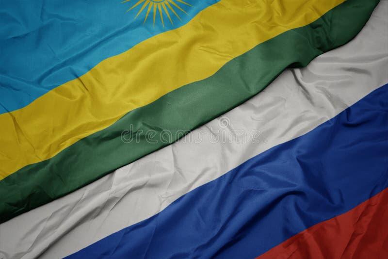 развевая красочный флаг России и национальный флаг Руанды стоковые фотографии rf