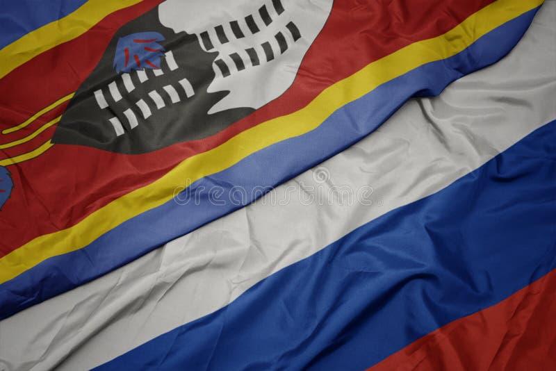 развевая красочный флаг России и национальный флаг Свазиленда стоковое изображение rf