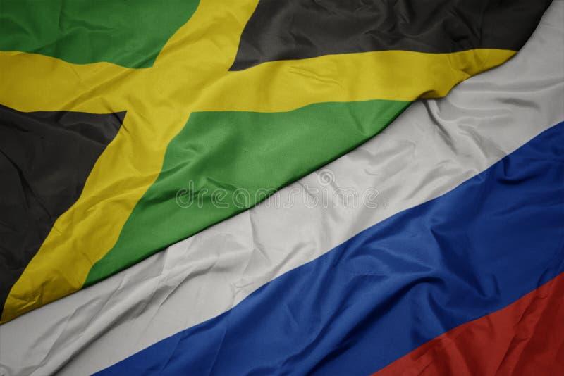 развевая красочный флаг России и национальный флаг Ямайки стоковые фотографии rf