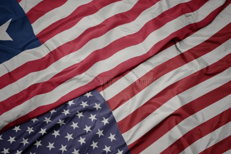 развевая красочный флаг Соединенных Штатов Америки и национальный флаг Либерии стоковые фотографии rf