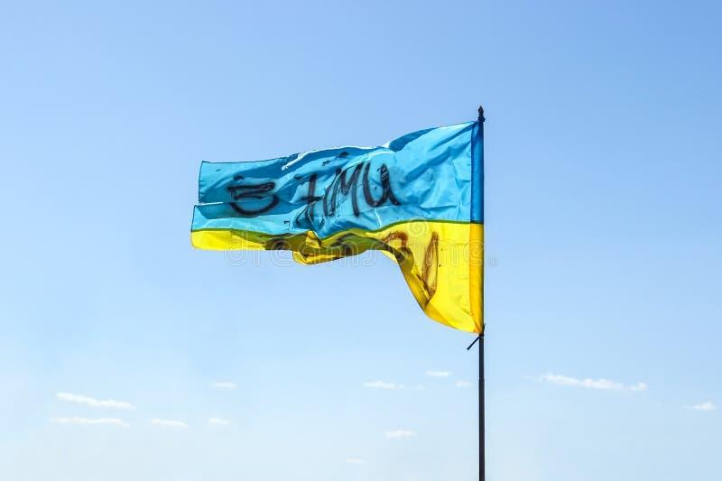 Развевая украинский желт-голубой флаг против голубого неба На флаге герб Украины и надписи стоковая фотография