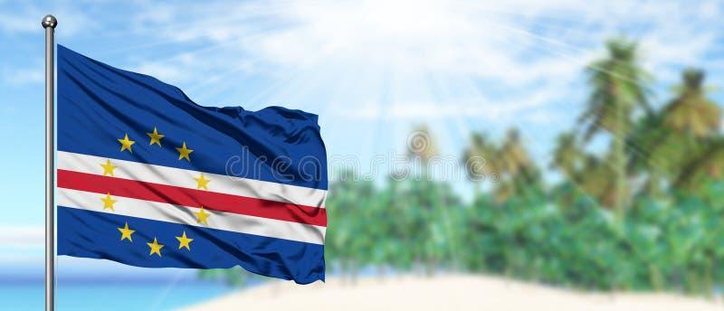 Развевая флаг Кабо-Верде в солнечном голубом небе с предпосылкой пляжа лета Отдыхает тема, концепция праздника стоковые изображения rf