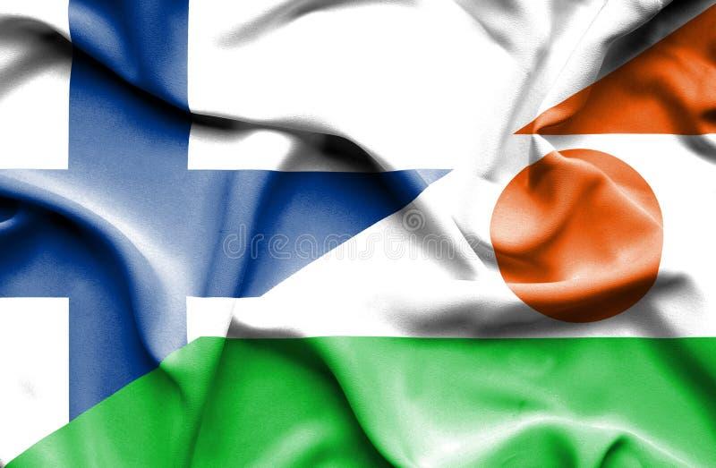 Развевая флаг Нигера и Финляндии стоковые фото