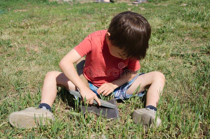 Разведчик мальчика точить ось стоковые изображения rf