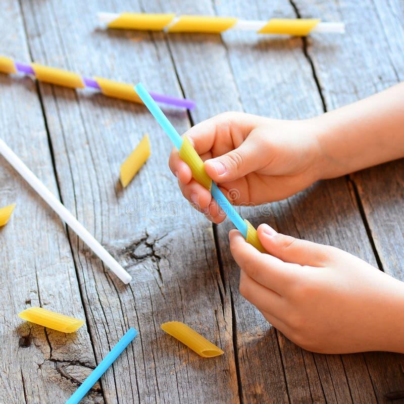 Развитие точных двигательных навыков в детях Малый ребенок держа солому и сырцовые макаронные изделия в его руках Деятельность пр стоковое изображение
