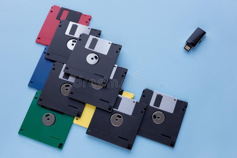 Развитие цифрового запоминающего устройства хранения данных Дискеты против небольшого внезапного привода Изолированный на голубой стоковое фото