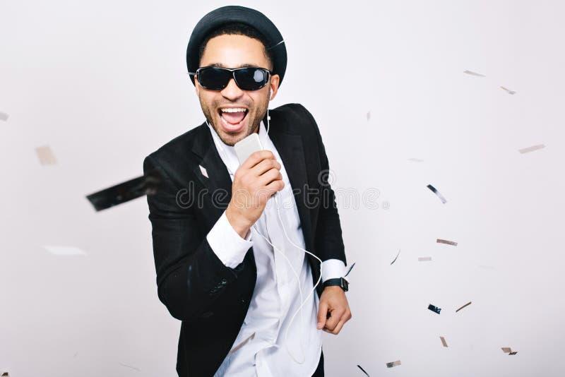 Развлечения, празднуя партию караоке возбужденного красивого парня в черных солнечных очках имея потеху на белой предпосылке стоковое фото rf