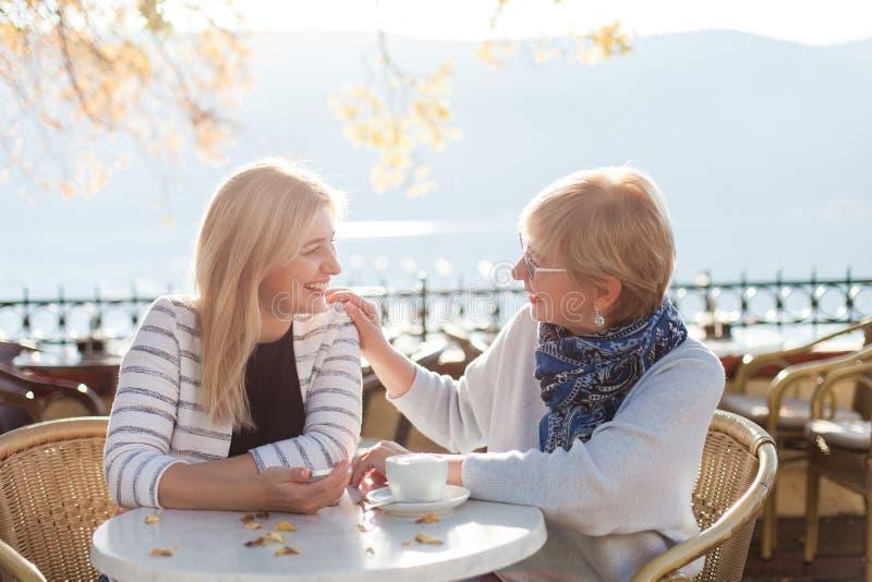 Разговор двух красивых женщин в уличных кафе Мать и ее взрослая дочь ведут диалог стоковое фото rf