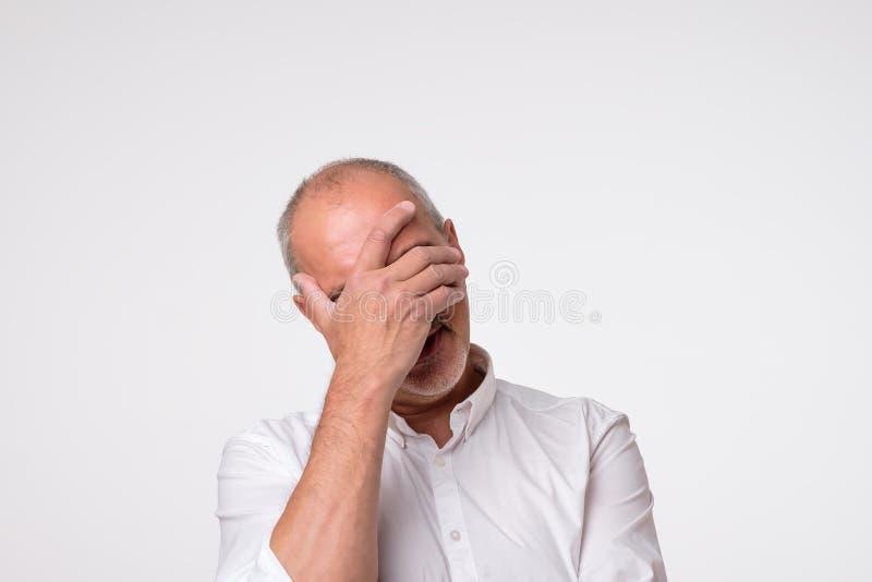 Раздражанный зрелый человек в белой рубашке покрывая его наблюдает стоковое изображение rf