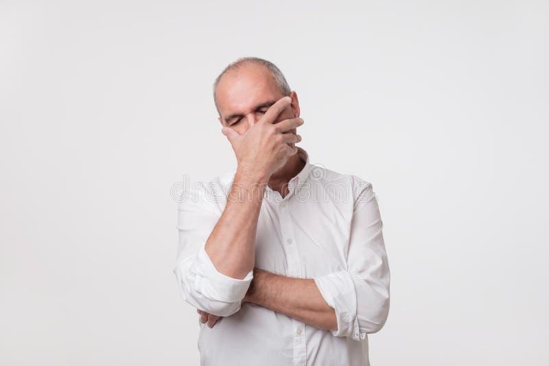 Раздражанный зрелый человек в белой рубашке покрывая его сторону с рукой над серой предпосылкой стоковое изображение rf