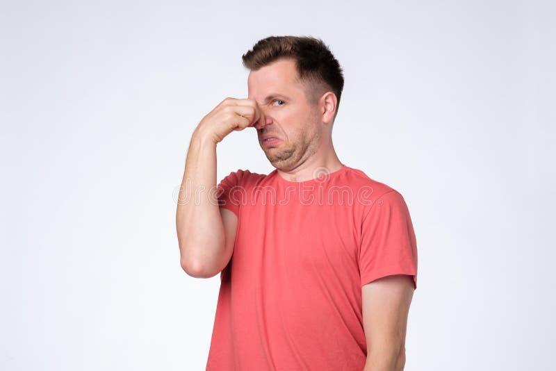 Раздражанный молодой человек затыкает нос как запахи что-то вонь и неприятное стоковые фотографии rf