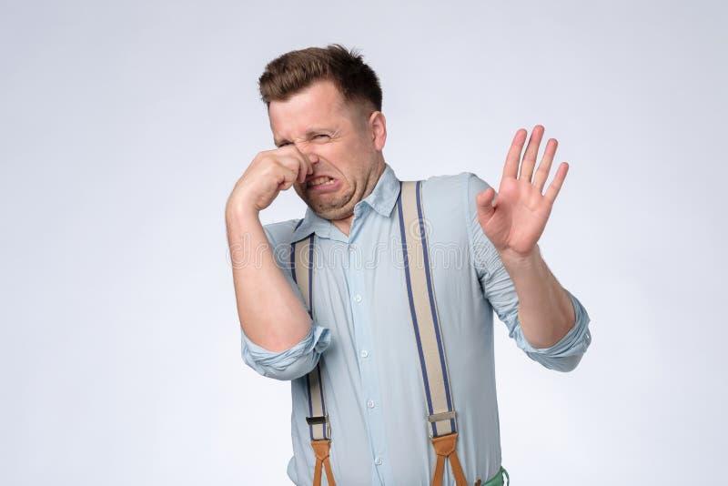 Раздражанный молодой человек затыкает нос как запахи что-то вонь и неприятное стоковые изображения rf