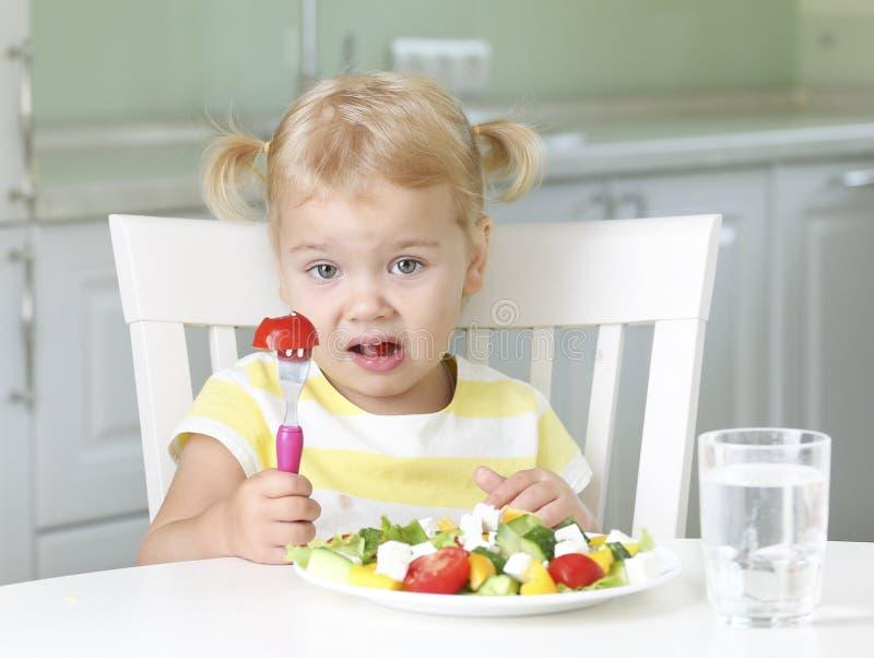 Раздражанный несчастный ребенок есть здоровую еду стоковое фото