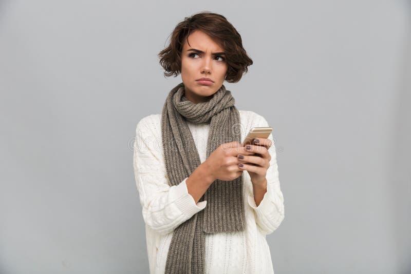 Раздражанный шарф молодой дамы нося беседуя мобильным телефоном стоковые изображения