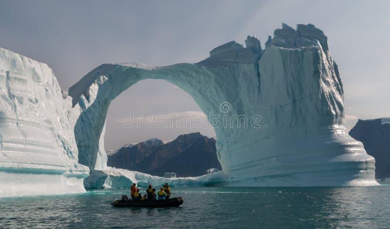 Раздувная шлюпка перед сводом айсберга, Гренландией стоковые фотографии rf