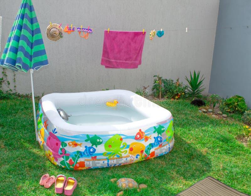 Раздувной бассейн в саде, с зонтиком стоковое изображение rf
