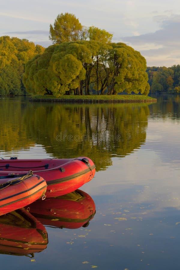Раздувные красные шлюпки на воде на реке или озере около берега в ясном летнем дне стоковое фото rf