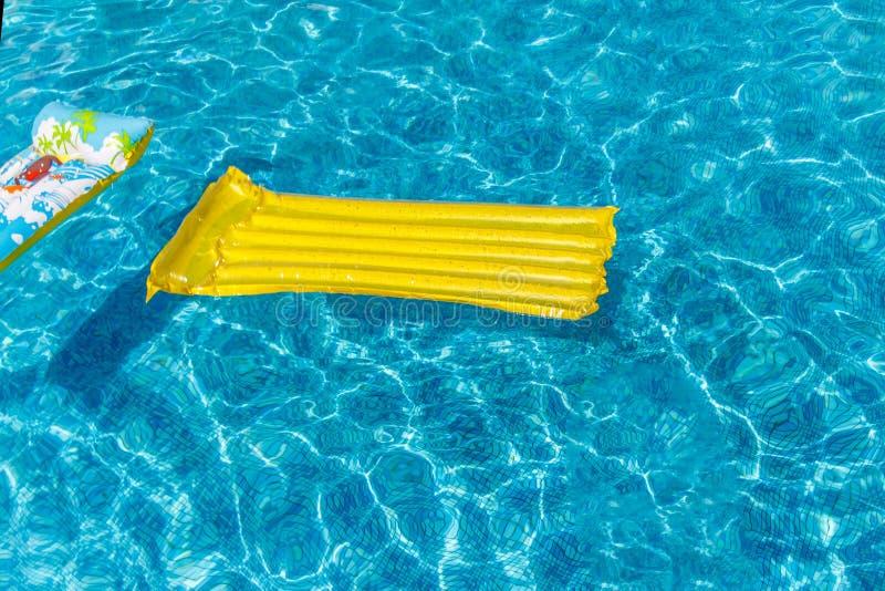 Раздувные тюфяки мероприятий на воде плавают на воду в бассейне Концепция, жизнерадостное, веселое яркое красочное лето и стоковые изображения