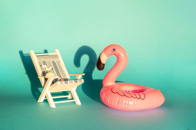 Раздувные фламинго и deckchair на голубой предпосылке, партия поплавка бассейна, стоковая фотография rf