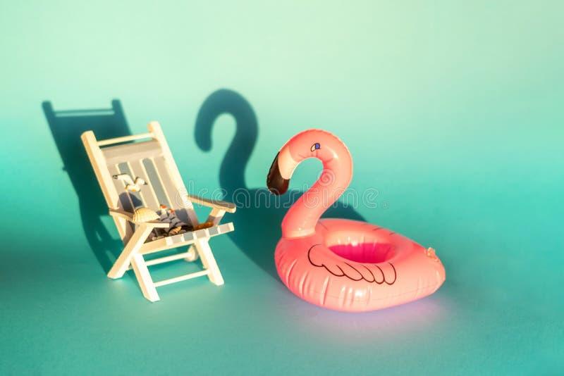 Раздувные фламинго и deckchair на голубой предпосылке, партия поплавка бассейна, стоковое изображение rf