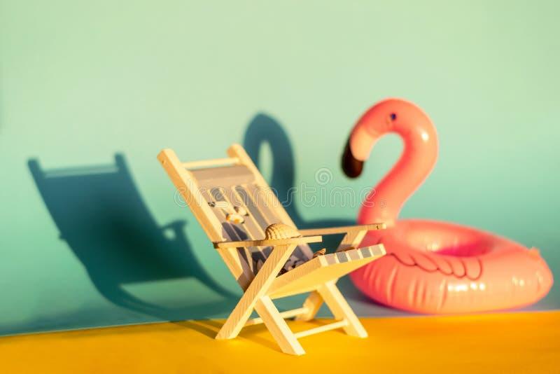 Раздувные фламинго и deckchair на голубой предпосылке, партия поплавка бассейна стоковое изображение
