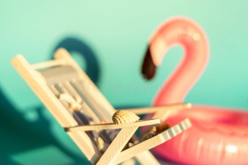 Раздувные фламинго и deckchair на голубой предпосылке, партия поплавка бассейна стоковое изображение rf