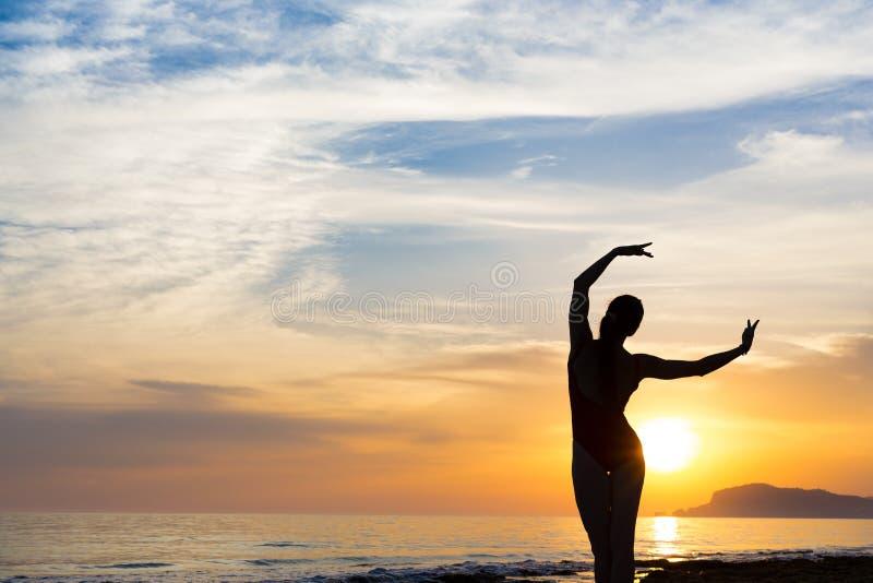 Раздумье женщины йоги захода солнца на побережье океана стоковая фотография