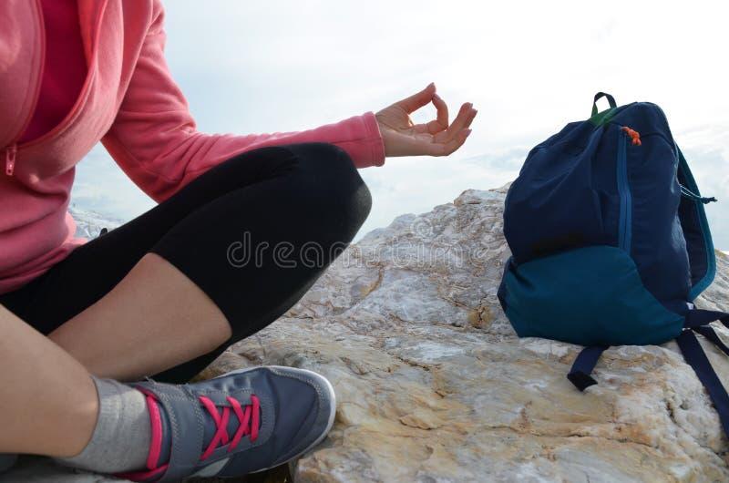 раздумье молодой женщины в представлении йоги на пляж девушка в положении лотоса на пустом каменном seashore принимает йогу, спор стоковое изображение