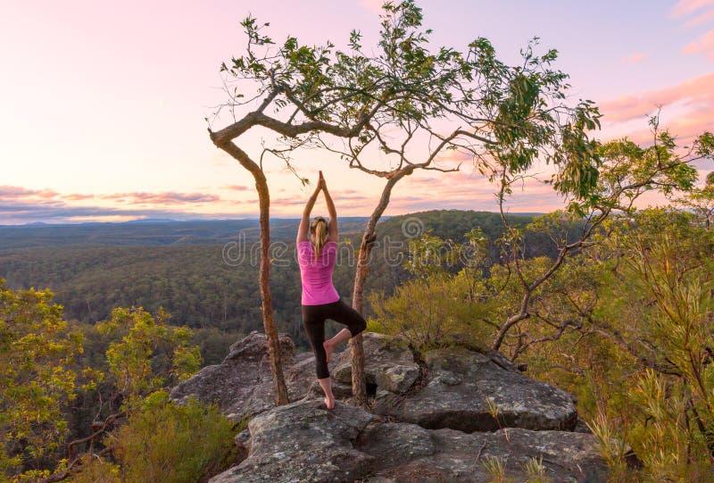 Раздумья йоги захода солнца от верхних частей скалы с взглядами стоковое фото