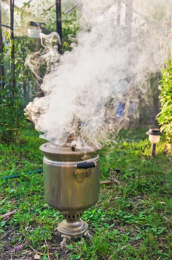 Разжигать самовар на швырке Зажигание древесины в старом самоваре стоковая фотография rf