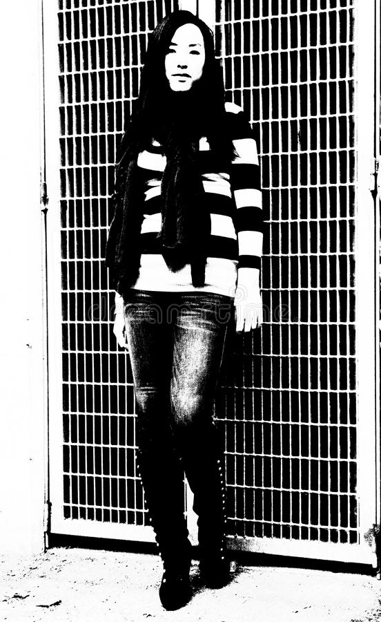 Разительный контраст в фото молодой женщины ее горизонтального striped свитера против предпосылки решетки в этом черно-белом изоб стоковые изображения